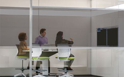 A man and two women are in a meeting presenting valuable information using a television screen which has been obscured to onlookers utilizing the Casper Cloaking Technology Window Film.