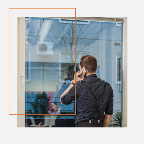 Man on phone looking through a window with 3M Window Film installed near Washington DC