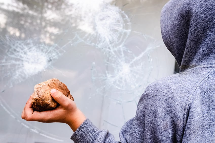 hooded criminal breaking glass window with a rock