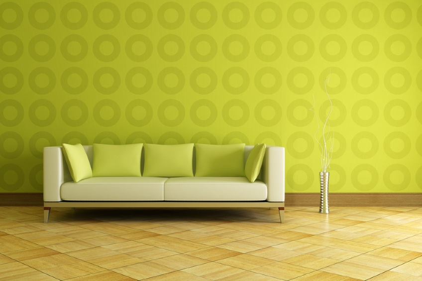 white and green couch in front a geometrical wallpaper
