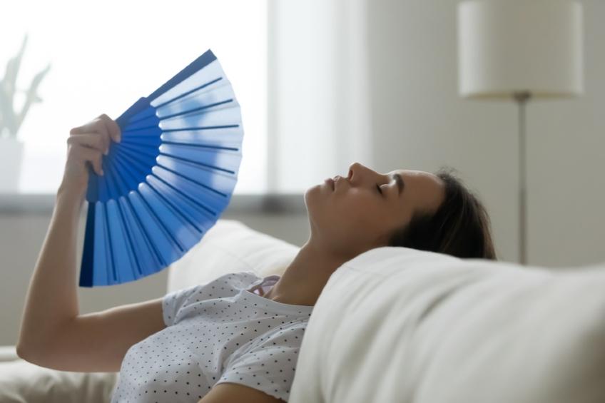 Woman feels sluggish due unbearable heat waves fan cooling herself