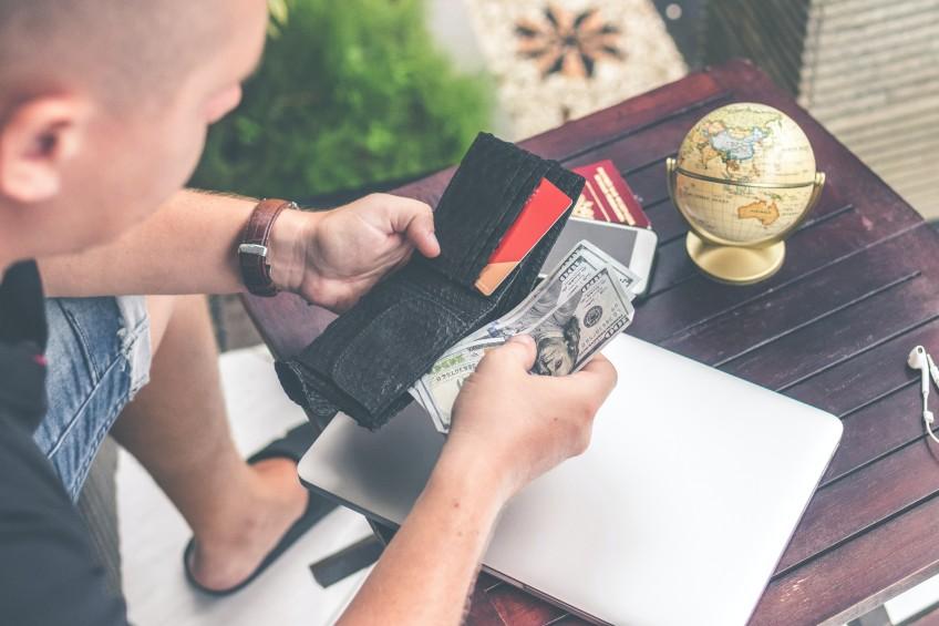 man putting hundred dollar bills back in black leather wallet